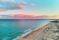 Picturesque scenery aerial drone view landscape, calm blue Mediterranean Sea colourful fluffy glowing pink clouds at sunset evening sky, sandy coastline. La Mata, Torrevieja, Costa Blanca, Spain