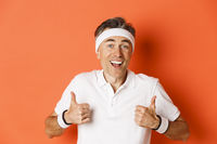 Close-up of cheerful middle-aged male athlete, wearing headband and t-shirt for workout, showing thumbs-up, approve something good, standing over orange background