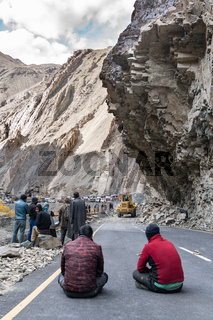 The group of truck drivers waiting when the road will be clear because of landslide
