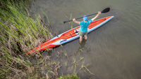 male stand up paddler stretching