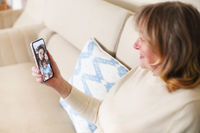 Woman talking with relatives during video call on smartphone
