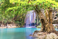 Waterfall in tropical forest with green tree and emerald lake, Erawan, Thailand