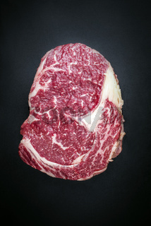 Raw dry aged wagyu entrecote beef steak as top view on a black background with copy space