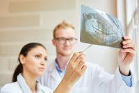 Zahnarzt und Zahnärztin mit Röntgenbild