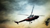 Blurred unrecognizable helicopter in a cloudy sky.