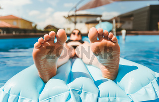 Young woman on pool air mattress in above ground pool.