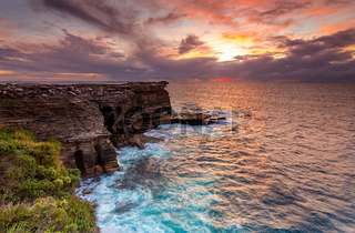Sunrise over the ocean and the crumbling headland cliffs