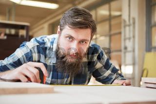 Hipster Mann mit Bart als Schreiner Lehrling