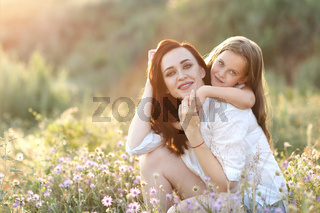 Content woman and girl hugging in field