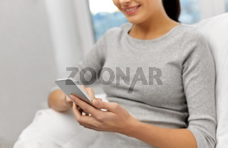 close up of happy woman with smartphone at home