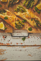 Baked green asparagus wrapped in puff pastry. Served on wooden board. With copy space