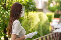 Waitress with face mask and face shield hold thermometer
