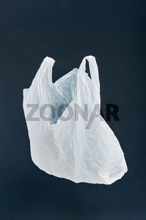 White empty plastic bag floating over black background