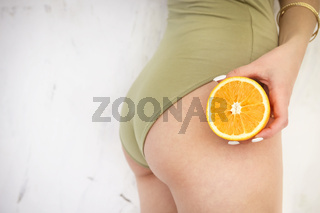 Young girl holding orange in her hand by the hips. Cellulite, liposuction, woman weight loss control concept