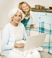 Grandmother And Little Grandchild Using Laptop At Home