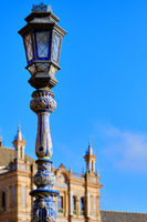Ceramic tiled lantern and Plaza de Espana ancient architecture on background against blue sky. Beloved famous touristic place, main landmark of Sevilla city Andalusia, Spain