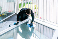 young male professional cleaner cleaning a large fold-down window