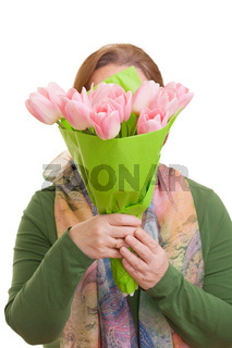 Elderly woman hiding behind a bouquet of colorful tulips, isolated on white background. Mothers day, Valentines day, Easter and surprise Concept.