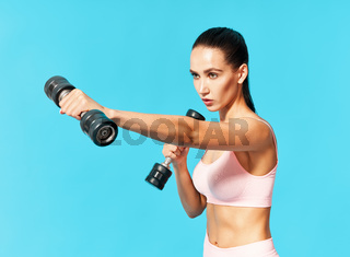 Young sporty woman in sportswear doing exercise with dumbbells on blue background