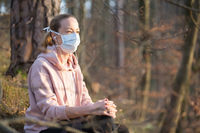 Portrait of caucasian sporty woman wearing medical protection face mask while relaxing in nature and listening to music. Corona virus, or Covid-19, is spreading all over the world