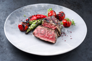 Barbecue dry aged wagyu roast beef steak with tomatoes and chili as closeup on a modern design plate