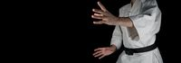 A person practicing aikido on a black background.