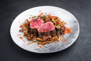 Barbecue dry aged beef fillet medallion steak natural with fried onion rings and mushrooms as closeup on a modern design plate with copy space