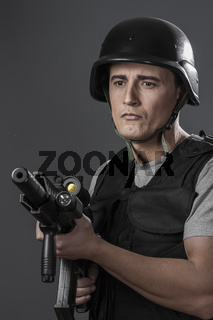 Safety, paintball sport player wearing protective helmet aiming pistol ,black armor and machine gun