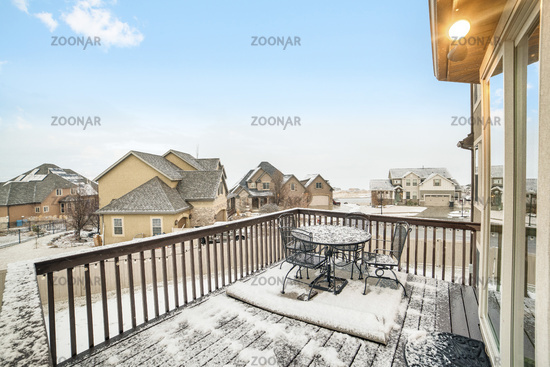 Snowy deck overlooking homes in the village blanketed with snow in winter