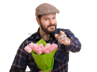 Bearded young handsome man with pointed indexfinger holding a bouquet of pink tulips, isolated on white background. Mothers day, Valentines day, Easter and surprise Concept.