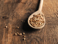 Organic buckwheat on a wooden spoon on a wooden kitchen table