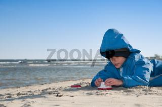 Kleiner Junge spielt am Strand mit Spielzeugschiff