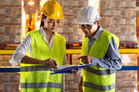 Asian warehouse manager discuss with worker