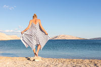 Happy carefree woman enjoying late afternoon walk on white pabbled beach on Pag island, Croatia