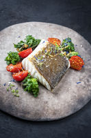 Gourmet fried European skrei cod fish filet with kalette and tomatoes as closeup on a modern design plate