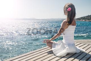 Woman meditating at the sea