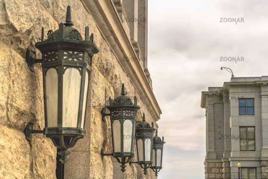 Vintage lanterns mounted on the stone wall at the exterior of a building