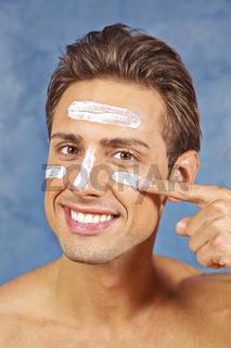 Mann pflegt seine Haut mit Gesichtscreme