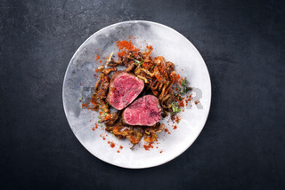 Barbecue dry aged beef fillet medallion steak natural with fried onion rings and carrots as top view on a modern design plate with copy space
