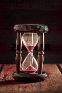 Time is running out concept. An hourglass with sand falling through, on a dark rustic background