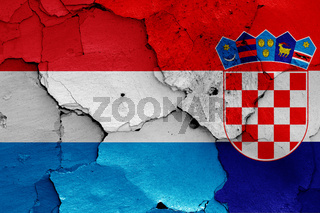 flags of Luxembourg and Croatia painted on cracked wall