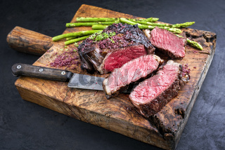 Barbecue dry aged wagyu rib-eye beef steak with green asparagus and red wine salt as closeup on an old rustic wooden cutting board