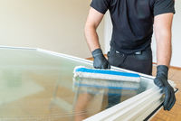 professional cleaner using a washer sleeve to soap and clean a large fold-down window