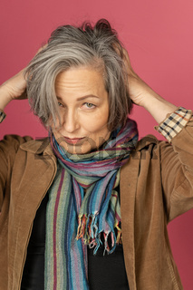 Graying mature woman making hairstyle, correcting her hair by hands. Creative lady gathered hair on back of her head posing in studio on pink background