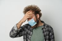 Suffer of headache wearing protective sterile medical mask on his face to protect coronavirus curly hair young man wearing plaid shirt and olive t-shirt under. White background