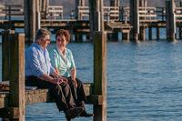 Verliebtes Seniorenpaar sitzt auf Bootssteg am Wasser