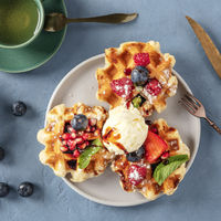 Waffles with fresh fruit, chocolate, caramel, and ice-cream, overhead square shot