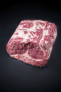 Raw dry aged wagyu entrecote beef steak roast as closeup on a black background with copy space