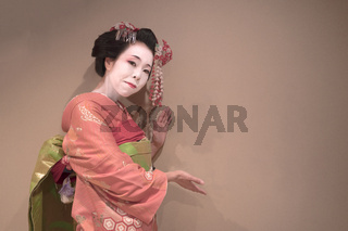 Clipping japanese geisha maiko girl in red kimono coifed hair brooch with patterns of red and white plum blossoms on white background.