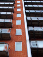 looking upwards view of modern apartment building with windows in brick walls and glass balconies